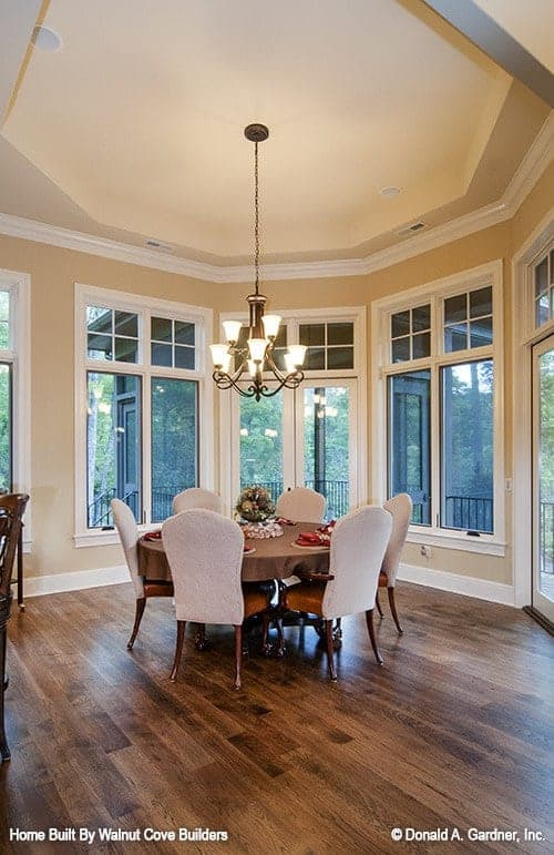 This is a simple dining area with beige walls and tall windows surrounding the round wooden dining table paired with white upholstered chairs and topped with a simple chandelier.