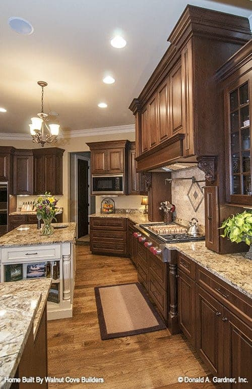 This is a close look at the kitchen that is dominated by the dark wooden cabinetry augmented by the warm lighting of the ceiling and the beige counters and backsplash that go well with the kitchen island.