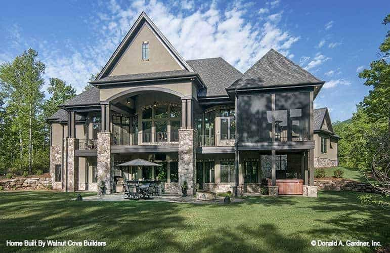 This is an exterior view of the back of the house that has mosaic stone flooring on its outdoor patio areas before transitioning to a grass lawn with tall trees on the sides.