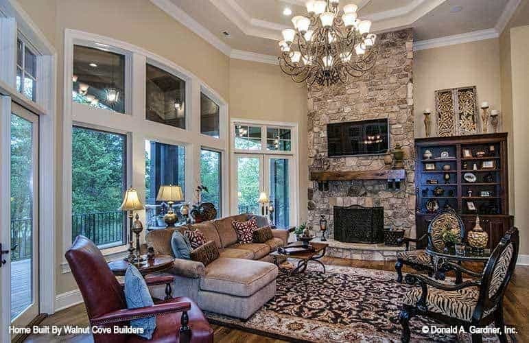 The living room is topped with a tall tray beige ceiling with a large chandelier over the patterned area rug paired with an L-shaped sectional sofa and a stone mosaic fireplace.