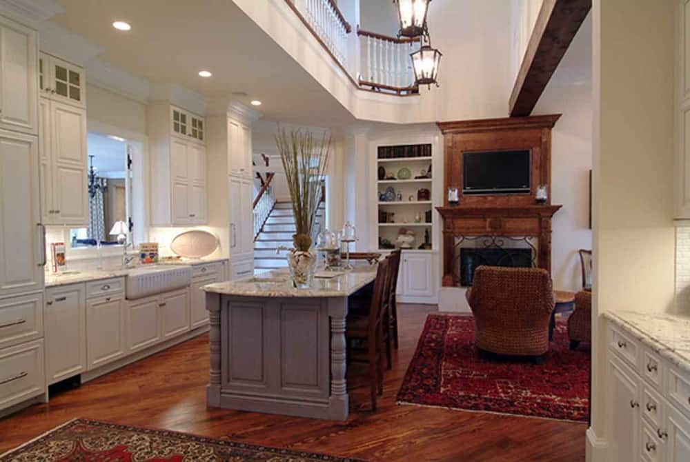 This is a look at the kitchen that has a tall ceiling with lantern pendant lights and an indoor balcony. The kitchen also has a gray wooden kitchen island paired with beige shaker cabinets and drawers lining the walls.