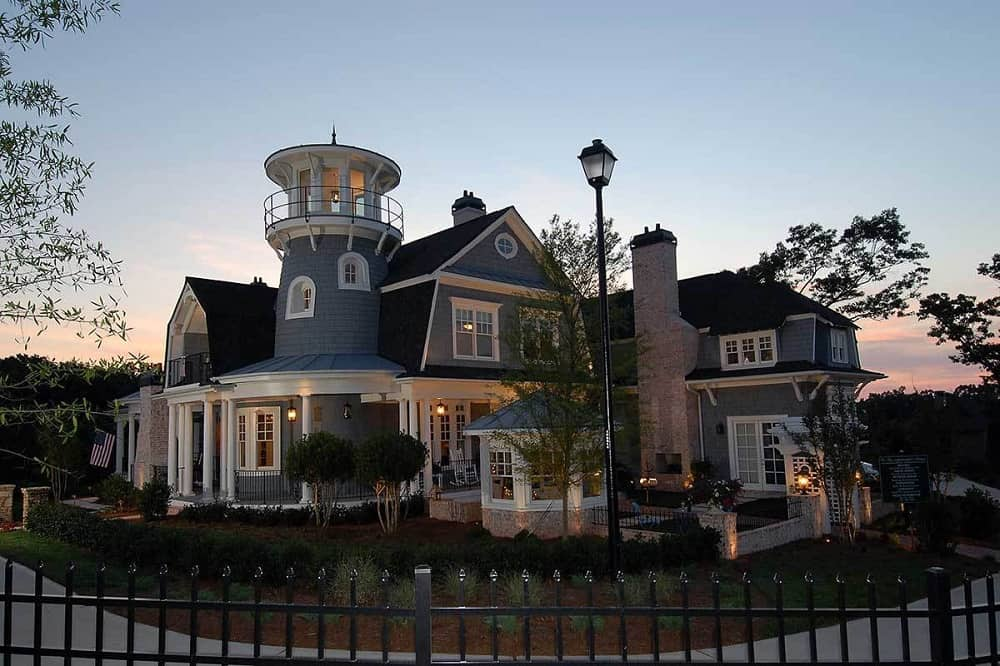 The shingle-style home has a tall lighthouse turret, gambrel roofs and gray exterior walls complemented by the landscaping of shrubs, medium-sized trees and outdoor lighting.