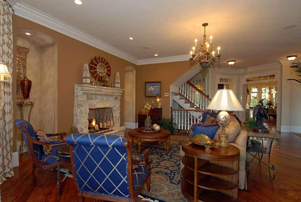 The living room has a large mosaic stone fireplace on a beige wall topped with decorations across from the beige sofa, wooden coffee table and the couple of blue cushioned armchairs on the patterned area rug.