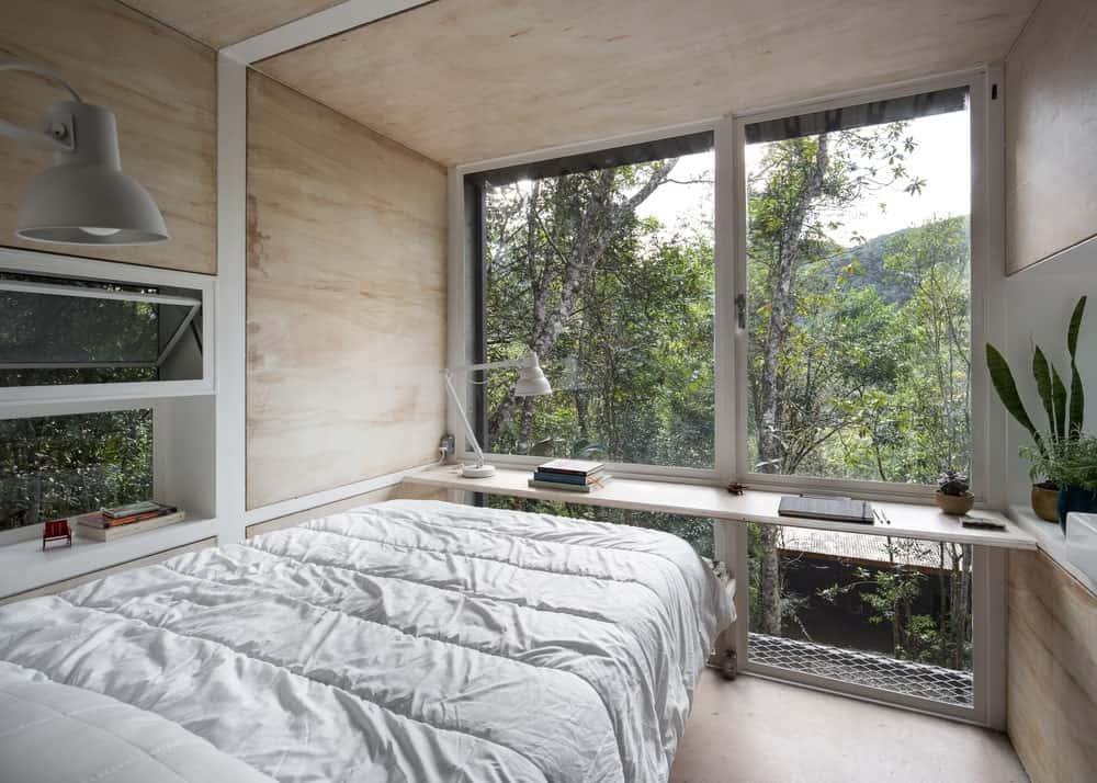 This is a close look at the bedroom with a cottage bed surrounded by light wooden structures with built-in shelves and a desk complemnted by the glass wall on the far side.