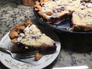 This is a sliced piece of blueberry lemon sour cream pie with crumble toppings.