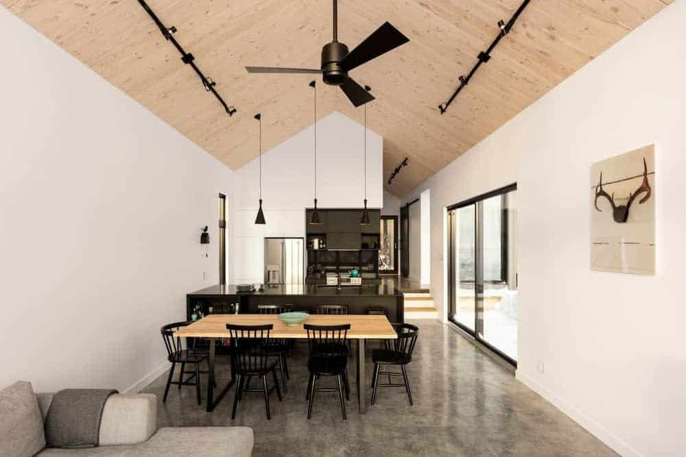 This is a view of the dining area placed in between the living room and kitchen that has a large wooden rectangular dining table surrounded by black wooden chairs and topped with a tall wooden shiplap cathedral ceiling.
