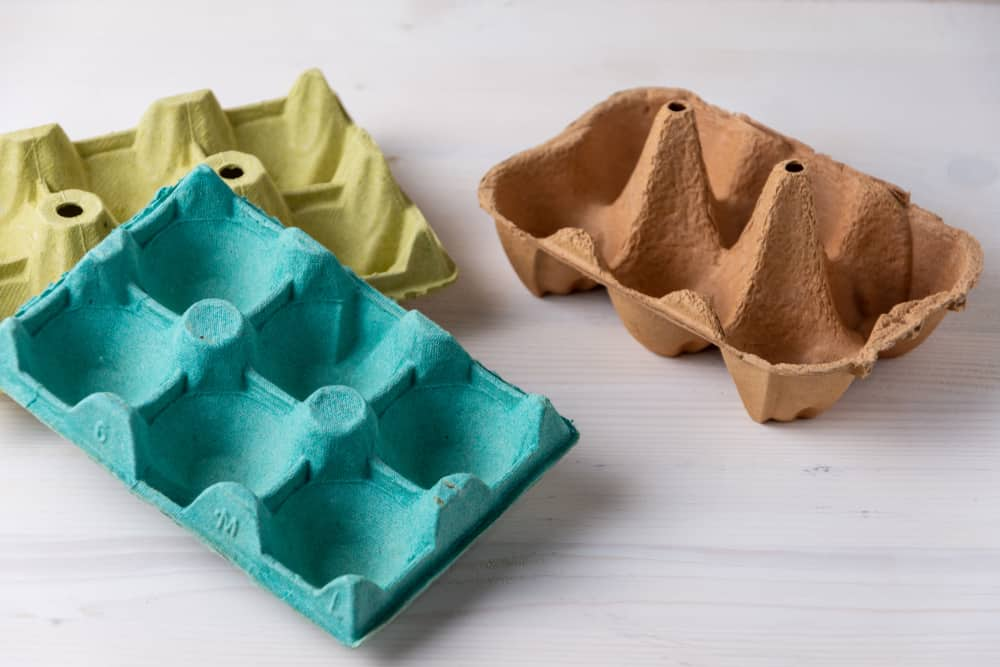 This is a close look at three sets of Cardboard Egg Cartons in various colors and design.
