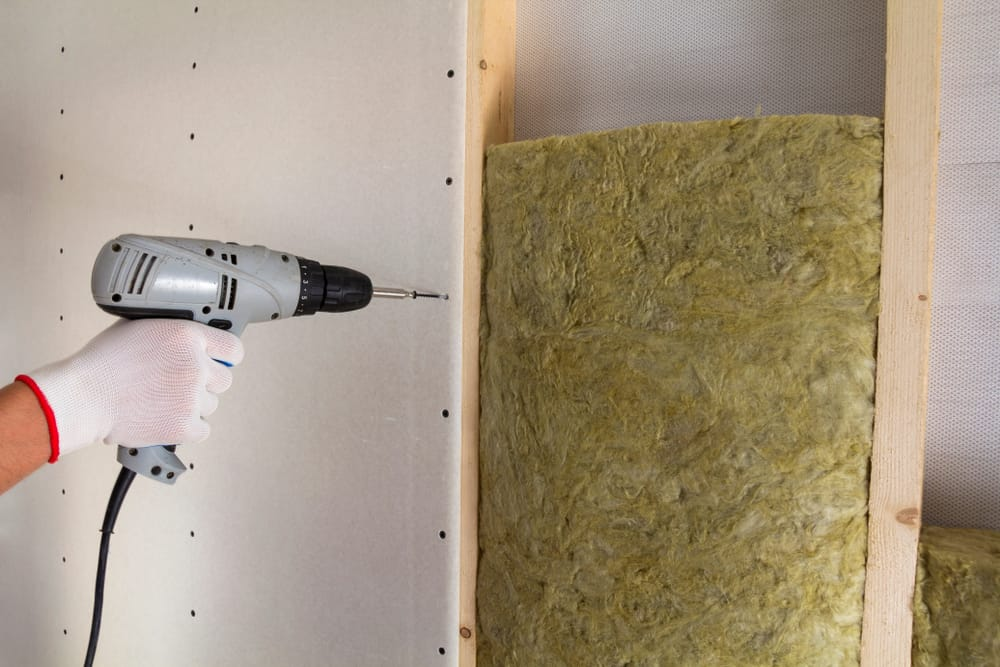 This is a close look at a man installing extra dry wall.