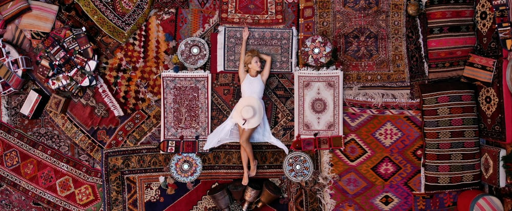 A woman lying on the floor that is filled with various carpets and rugs.