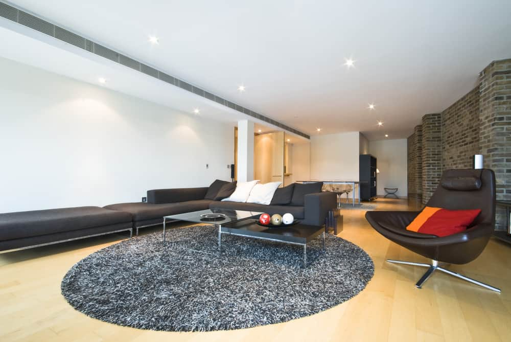 This is a full view of a living room with a large black leather sectional sofa paired with a round area rug on the light hardwood flooring.