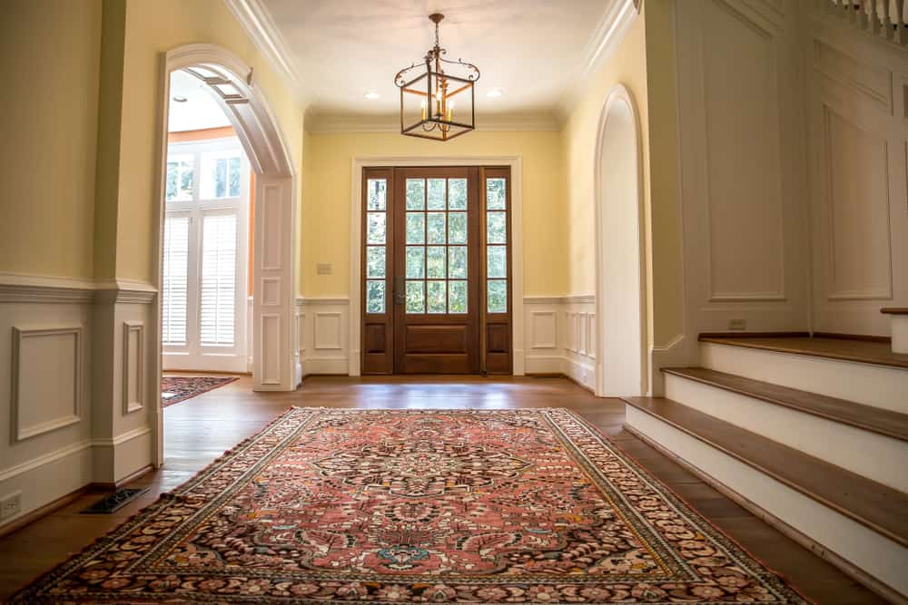 This is a simple foyer that has hardwood flooring topped with a colorful patterned oriental rug.