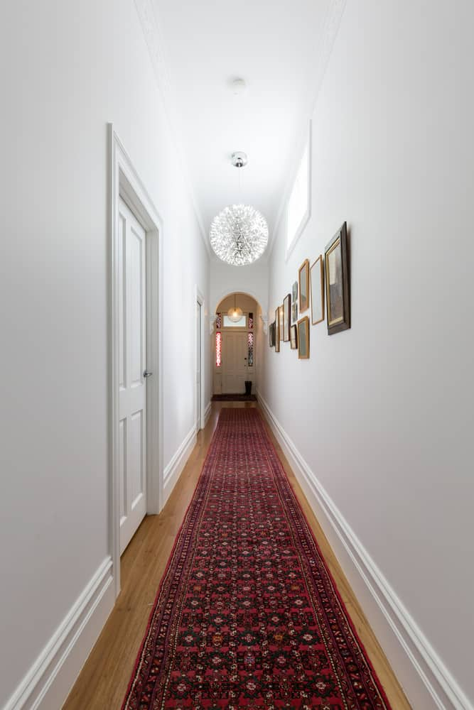 This is a long hallway with white walls and hardwood flooring covered with a red patterned runner rug.