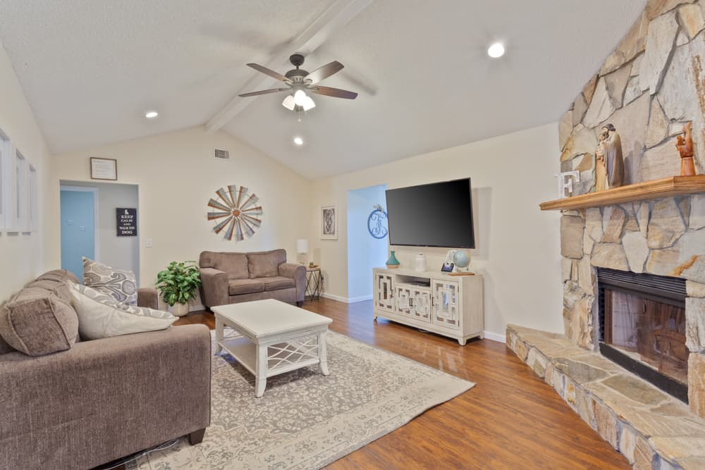 This is a living room with a couple of sofas, mosaic stone fireplace and a patterned gray area rug.