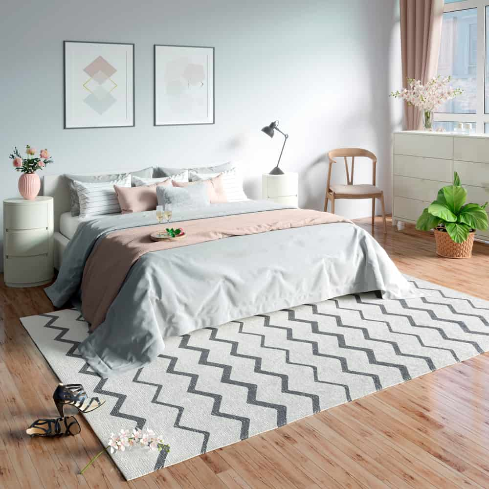 This is a bright bedroom with a large bed adorned by the patterned area rug by the foot.