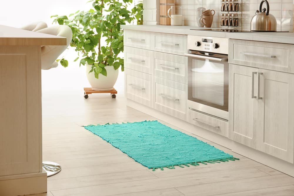 This is a close look at the bright kitchen that is adorned with a brightly-colored small rug by the cooking area.