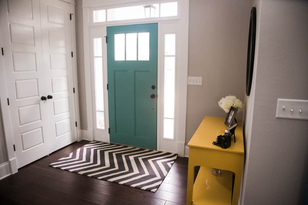This is contemporary foyer with a green door, a yellow console table and a patterned area rug.