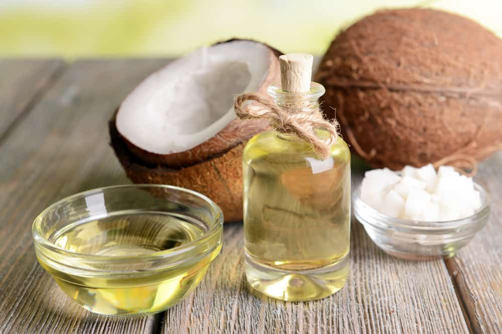 processed bottle of coconut oil sitting on a wooden table next to a cracked coconut