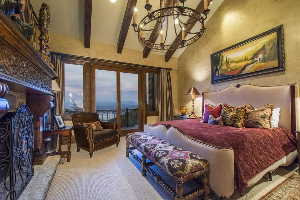 The primary bedroom has a large bed topped with an arched ceiling with exposed wooden beams and a wrought-iron chandelier. These are then complemented by the colorful artwork and the glass wall.