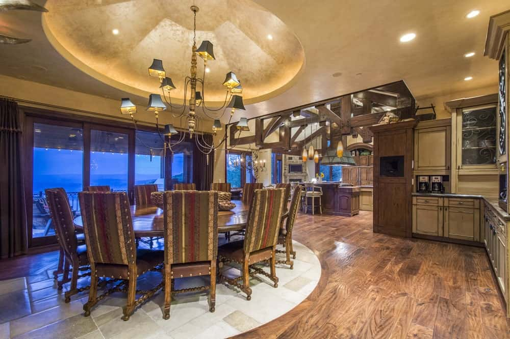This is the formal dining room with a large wooden circular dining table topped with a decorative chandelier from a dome ceiling. These are then complemented by the hardwood flooring.