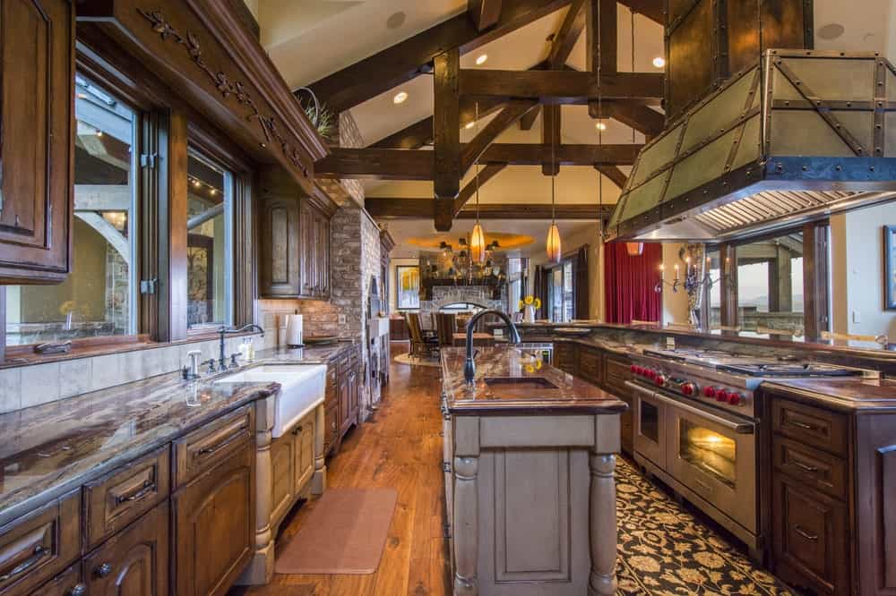 This is the spacious kitchen with a large kitchen island and tall cathedral ceiling that has exposed wooden beams. These are then complemented by the dark wooden cabinetry and hardwood flooring.