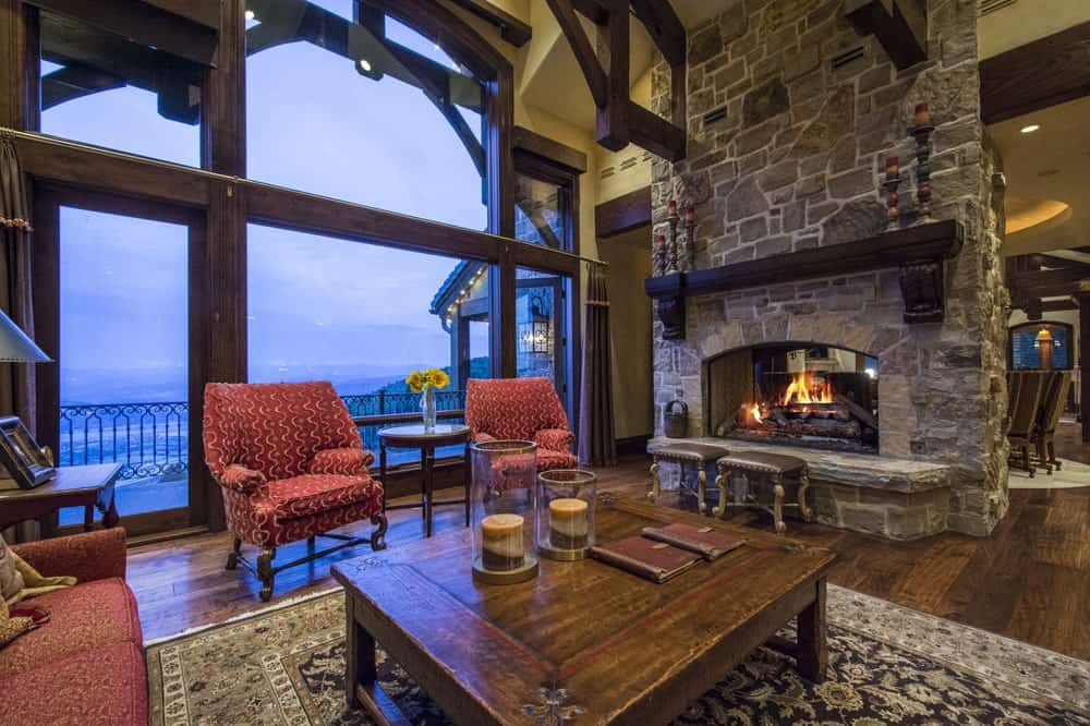 This is the living room that has a large stone fireplace to warm the comfortable cushioned chairs surrounding the wooden coffee table. This also shows a large glass wall.