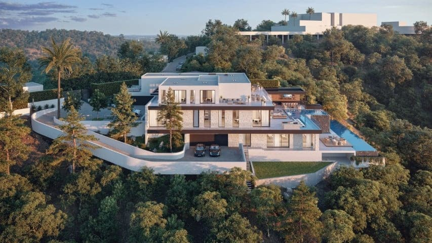 This is an aerial view of the hillside mansion showcasing the three levels, two pool terraces and an abundance of glass walls and doors. There is also a concrete driveway leading to the garage below. Image courtesy of Toptenrealestatedeals.com.