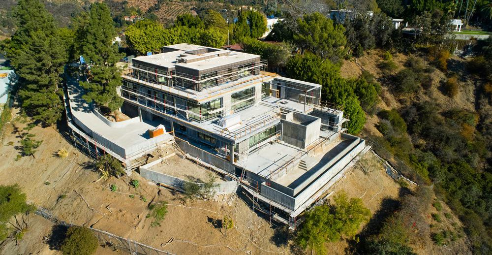 This is an aerial view of the house during its construction phase showcasing the concrete structures that support the house as well as the pool terraces. Image courtesy of Toptenrealestatedeals.com.