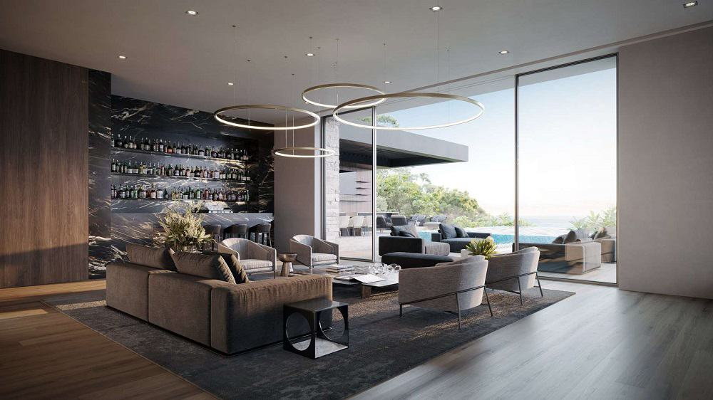 This is a look at the living room of the house with gray cushioned armchairs and a large sofa surrounding a large square coffee table topped with multiple modern lighting. These are then brightened by the glass doors leading to the pool area. Image courtesy of Toptenrealestatedeals.com.