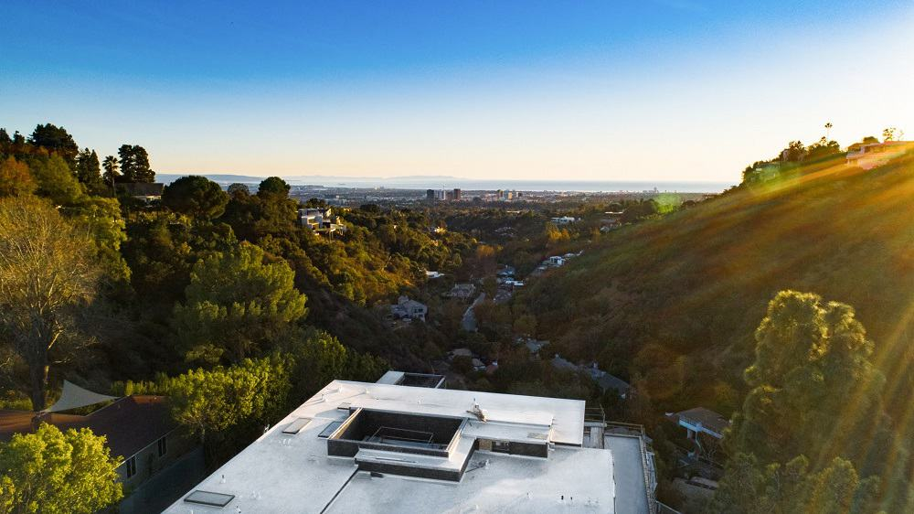 This is an aerial view of the house's concrete rooftop and the view of the valley, city and sea beyond. You can also see here the tall trees flanking the property. Image courtesy of Toptenrealestatedeals.com.