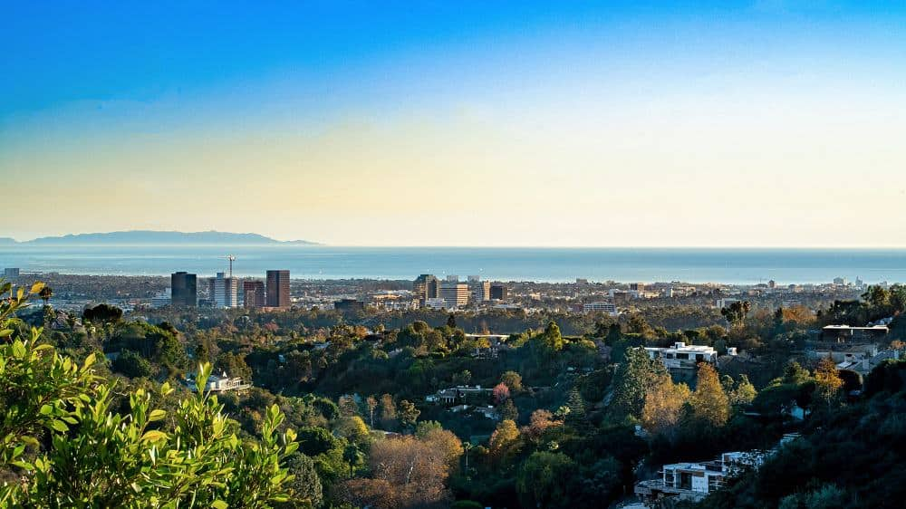 This is a closer look at the view with a focus on the city and the and sea. You can see here the tall buildings and the tall trees that augment the view. Image courtesy of Toptenrealestatedeals.com.