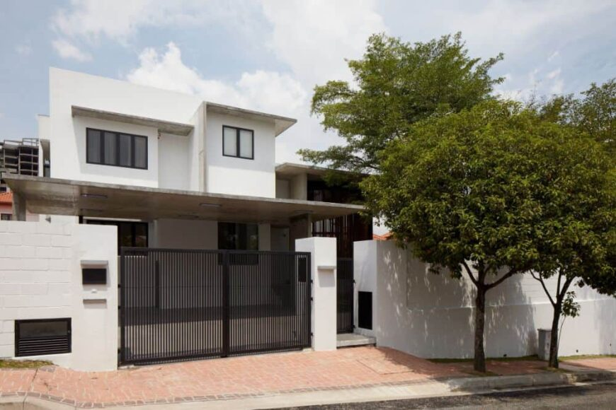 This is a view of the front of the house showcasing the slatted design of the outer gate and the white exterior walls of the house.