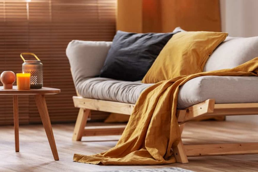 THis is a close look at a living room that has a scandinavian-style sofa with adjustable sides to convert to a futon.