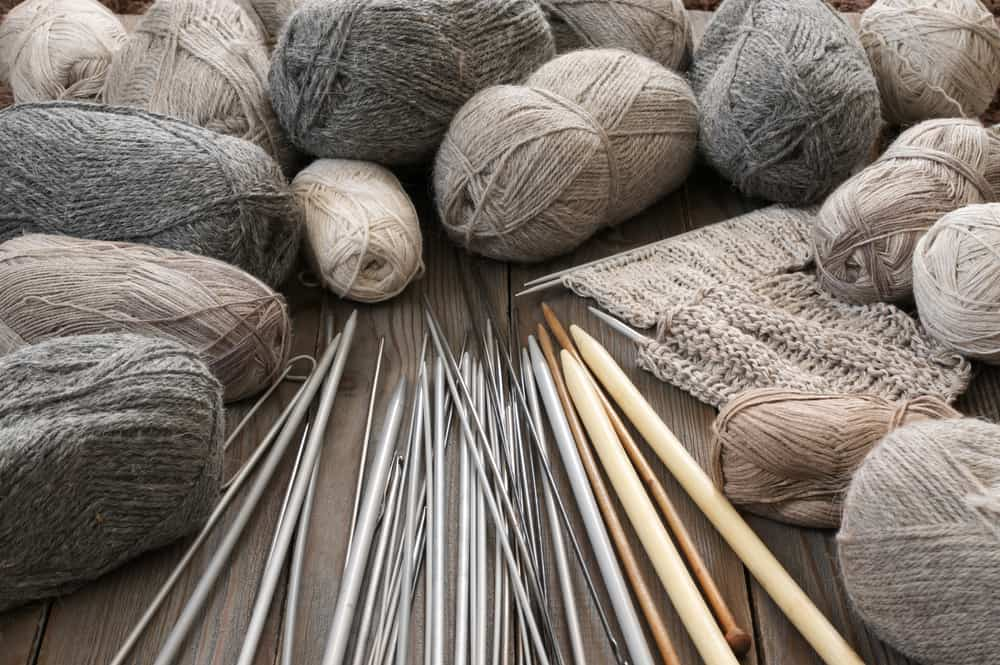 A collection of various yarn along with a variety of knitting needles.
