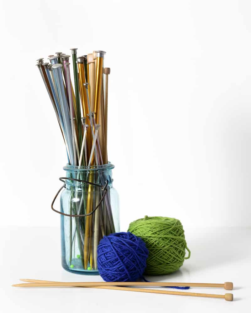 This is a couple of thread spools beside a jar filled with knitting needles.