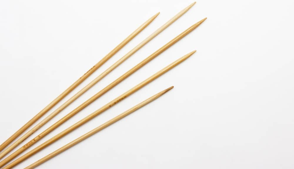 This is a close look at various straight knitting needles on a white surface.