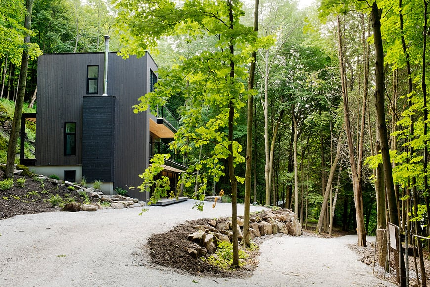 This is a far-off view of the chalet home surrounded by a lush landscape of graveled driveway, tall trees and stone structures.