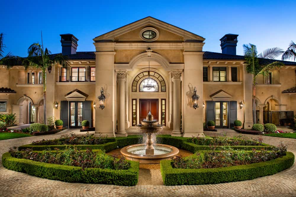 This is the front of the main house with a cobbled driveway, a fountain, a round garden and a façade with pillars and arches. Image courtesy of Toptenrealestatedeals.com.