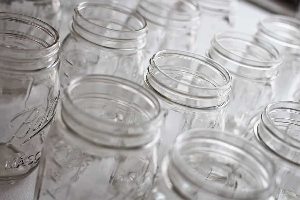This is a close look at bunch of glass mason jars with open lids.