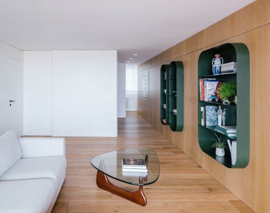 This is a close look at the living room with a white sofa paired with a glass-top coffee table on a hardwood flooring.