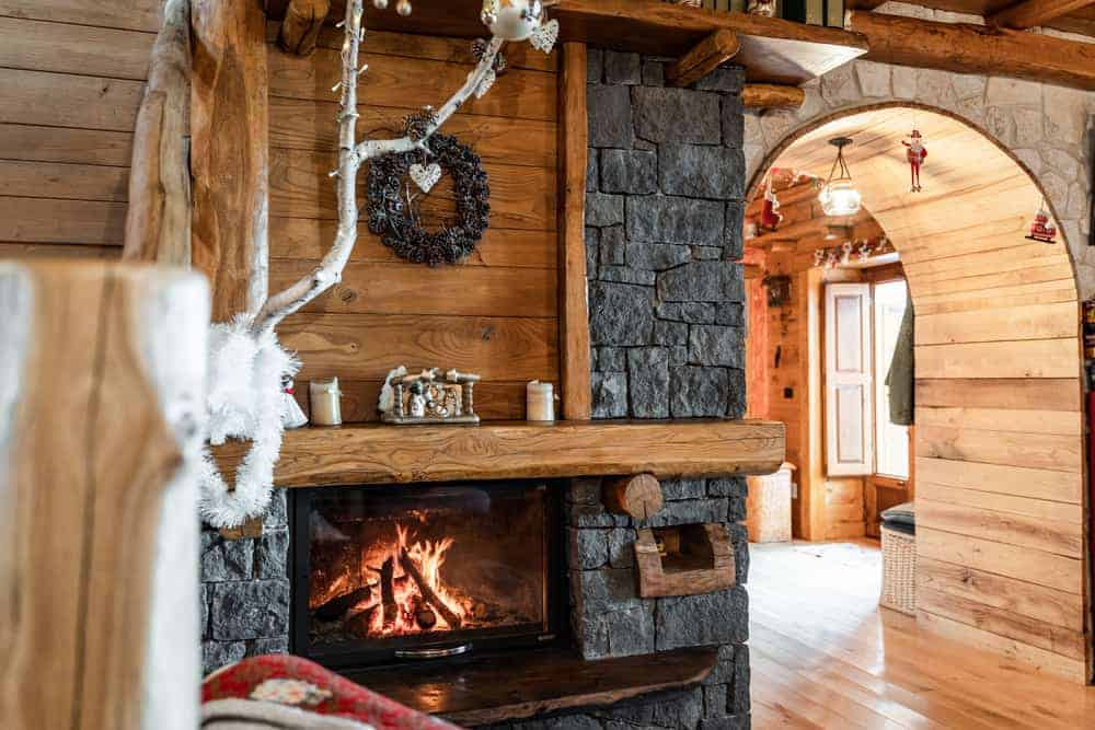 This is a close look at the interiors of the house that has wooden accents and dark gray mosaic stone walls that house the rustic fireplace beside the arched entryway.