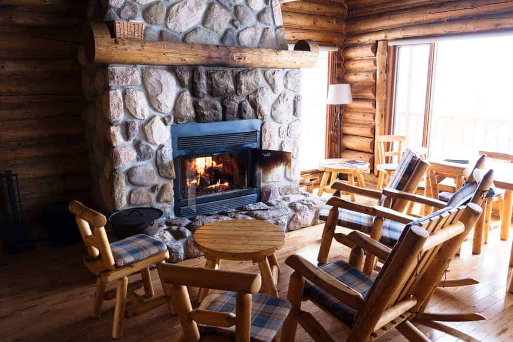 This is a close look at the living room of a chalet that has a stone mosaic fireplace across from the rustic sets of chairs that match the log beams of the walls.