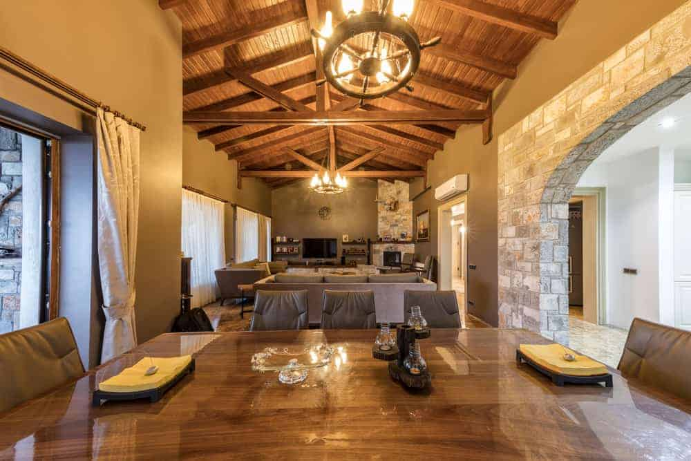 This is a look at the interior open plan of the great room that has a tall wooden cathedral ceiling with exposed beams and round chandeliers over the dining and living room areas.
