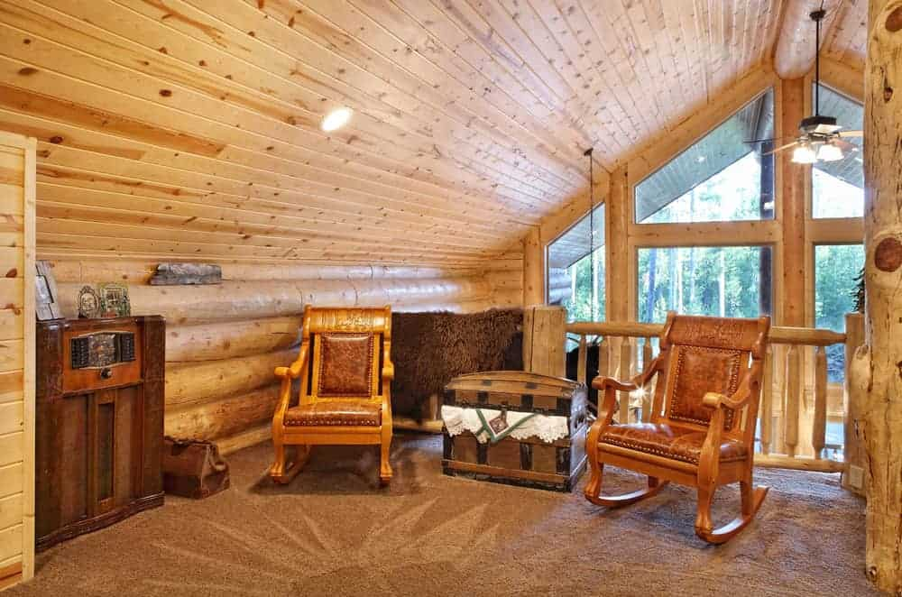 This is a close look at the loft and indoor balcony over the living room area. It has a wooden shiplap ceiling and a couple of wooden armchairs on a patterned area rug.