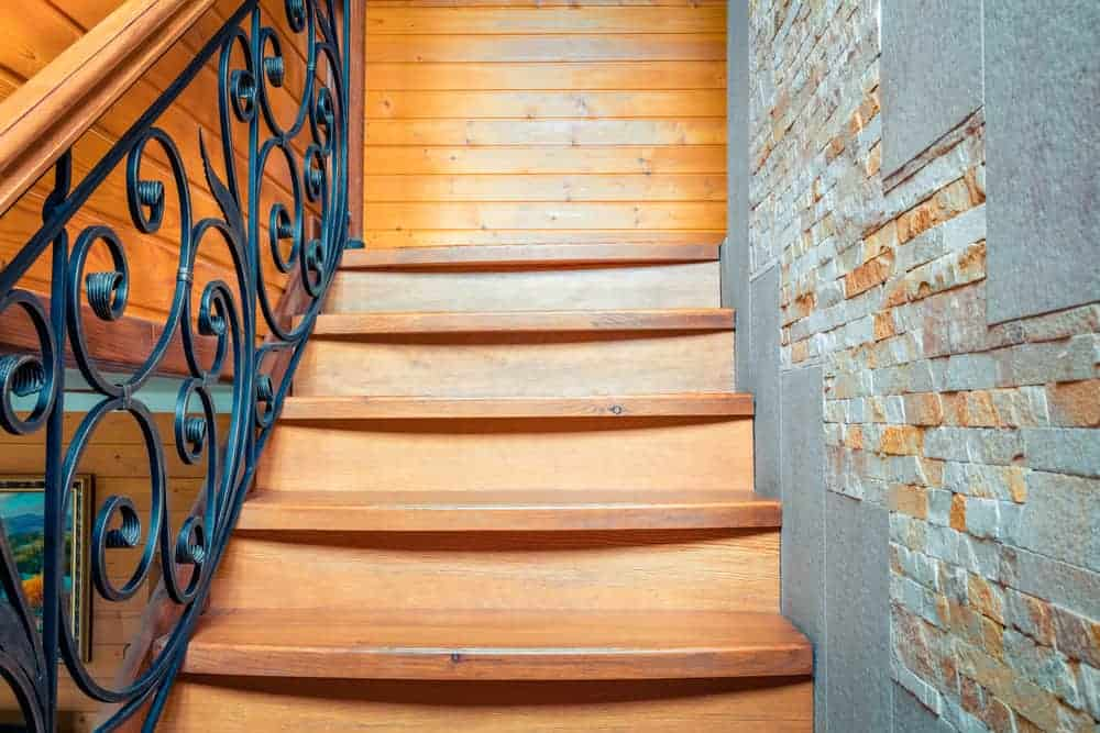 This is a close look at the wooden staircase of the house with a textured stone wall on the side and a set of intricate wrought iron railings.