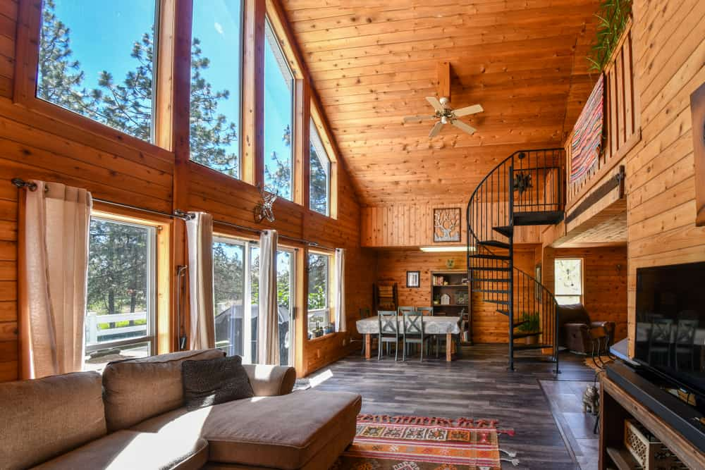 This is a look at the interiors of a mountain chalet-style home with a tall wooden shiplap ceiling over a great room that houses the dining, foyer and living room areas.