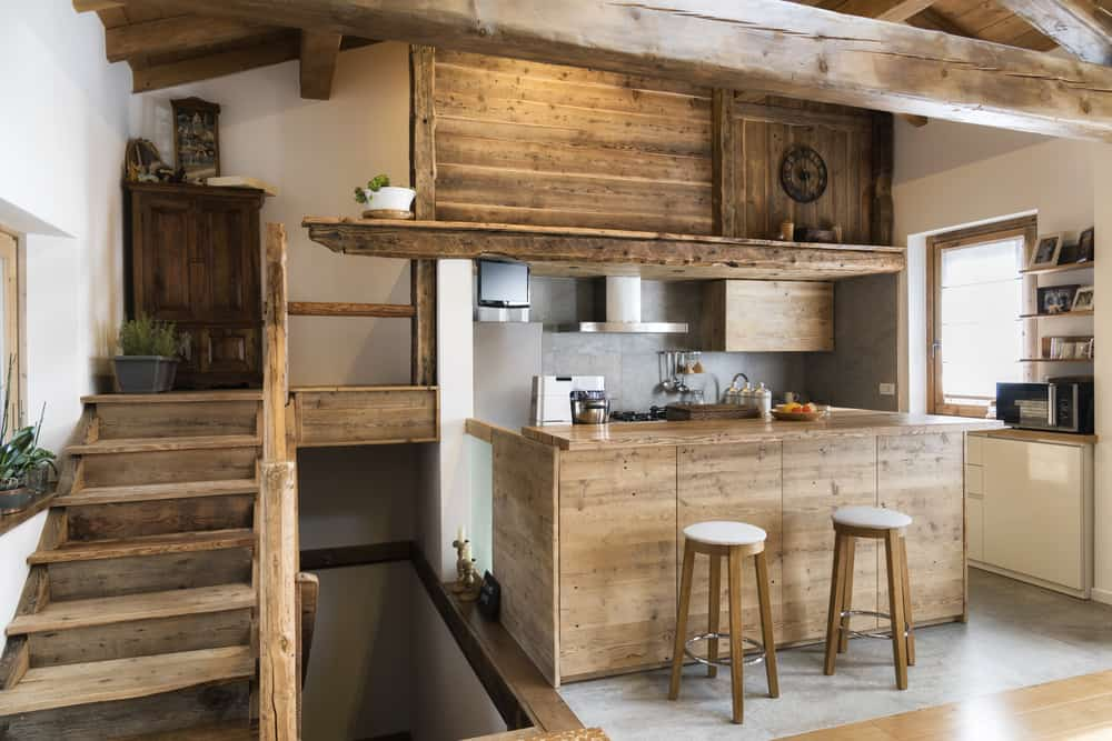 This is a close look at the chalet-style kitchen that has consistent wooden structures like the wooden peninsula and the wooden sccent above it to match the staircase on the side and the exposed beams of the ceiling.