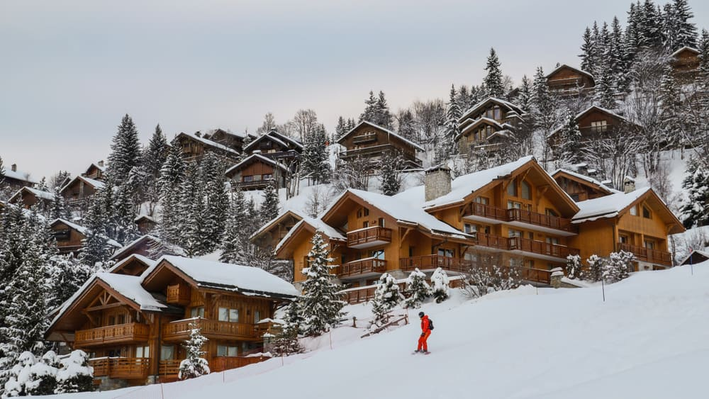 This is a mountain chalet ski resort with multiple wooden structures and houses on the slope with tall pine trees.