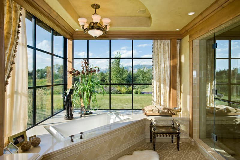 The primary bathroom has a large corner bathtub under large windows topped with a chandelier hanging from a tray beige ceiling.