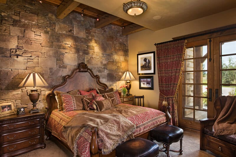 This is a close look at the bedroom that has a large wooden bed complemented by the large mosaic stone wall behind the headboard augmented by the warm lighting and exposed beams.