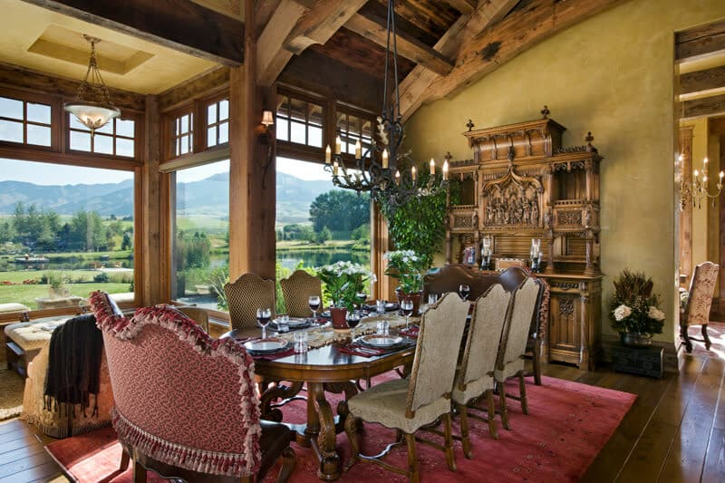 This is a close look at the formal dining room that has a large wooden dining table topped with a cathedral beamed ceiling and brightened by the glass windows.